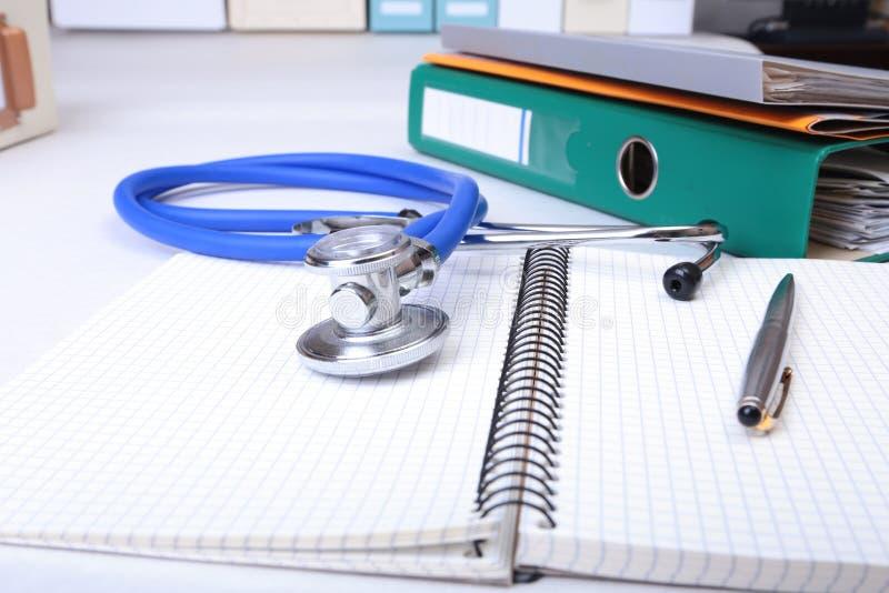 Arquivo do dobrador, estetoscópio e prescrição de RX na mesa Fundo borrado fotografia de stock