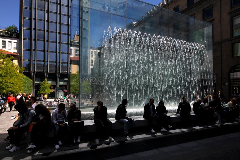 Arrêt au pied du parallélépipède en cristal d'Apple Store dans la liberté de Piazza à Milan photo libre de droits