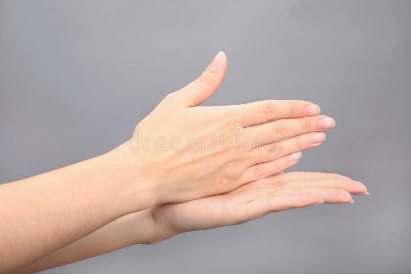 Arrêt de mot d'apparence de femme sur le fond gris Langue des signes photos stock