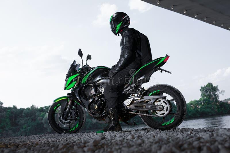 Arrêt de motocycliste sous le pont au-dessus de la pluie de attente de route à arrêter photo stock