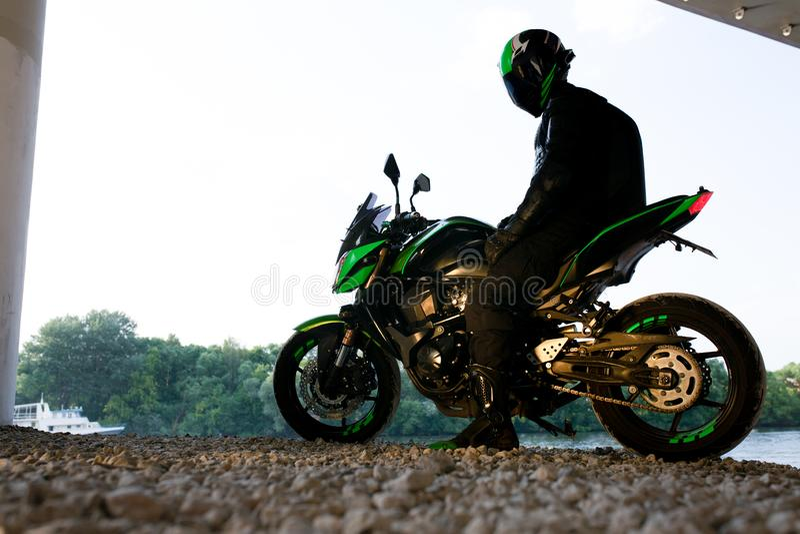 Arrêt de motocycliste sous le pont au-dessus de la pluie de attente de route à arrêter images libres de droits