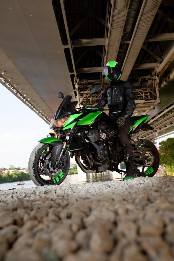 Arrêt de motocycliste sous le pont au-dessus de la pluie de attente de route à arrêter photographie stock libre de droits
