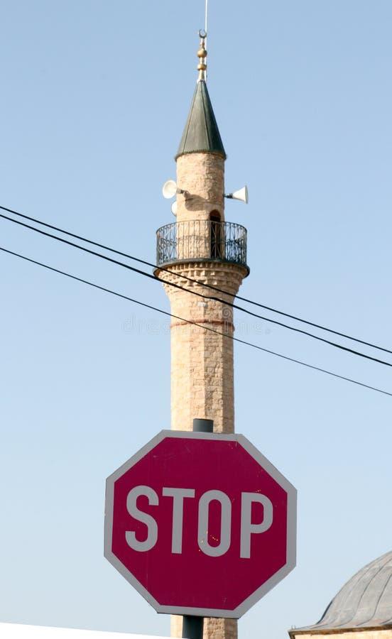 Arrêt de poteau de signalisation devant le minaret et la religion photos libres de droits