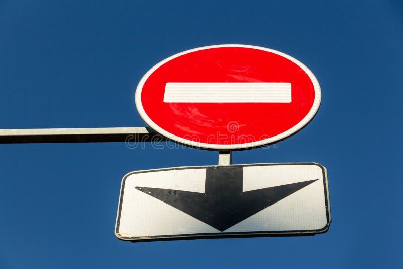 Arrêt de poteau de signalisation et flèche noire sur le fond de ciel bleu Signe de prohibition images stock