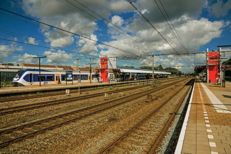 Arrêt locomotif sur la plate-forme de station de train, les rails de chemin de fer et le ciel nuageux bleu chez Weesp photographie stock libre de droits