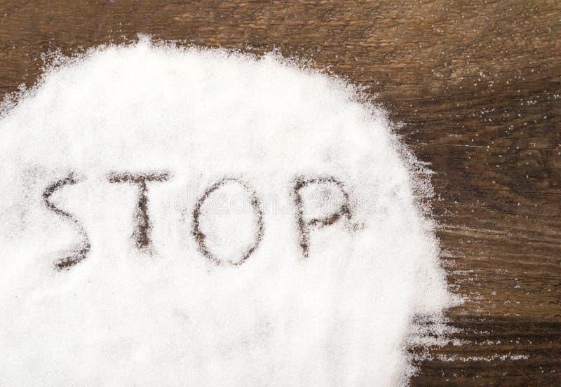 Arrêtez le signe fait de sucre granulaire photos stock