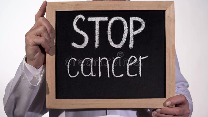 Arrêtez le texte de cancer sur le tableau noir dans des mains de docteur, innovations de thérapie de la maladie images stock