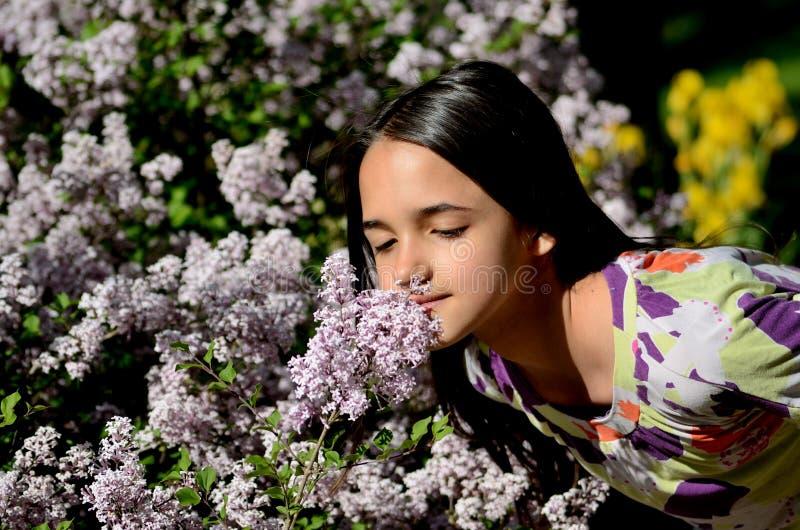 Arrêts de petite fille pour sentir les fleurs photos libres de droits