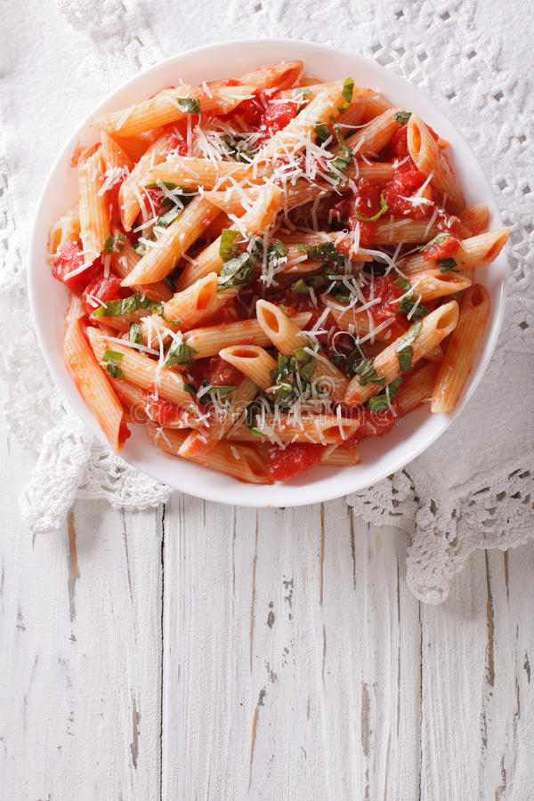 Arrabiata pasta penne with Parmesan cheese. vertical top view. Arrabiata pasta penne with Parmesan cheese on a plate. vertical top view royalty free stock images