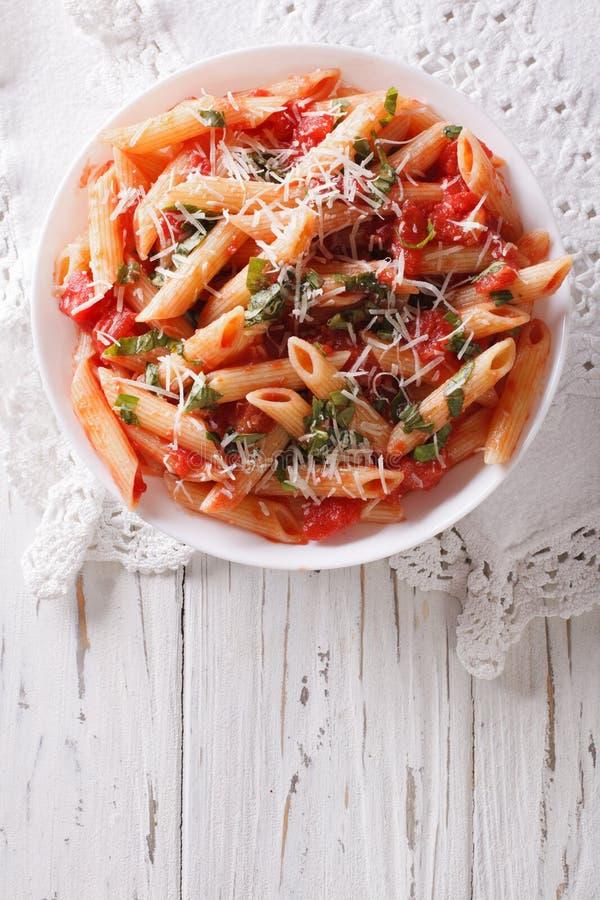 Arrabiata pastapenne med parmesanost Vertikal bästa sikt royaltyfria bilder