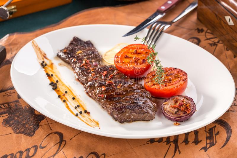 Arrachera mexican spiced skirt steak with grilled tomatoes and onion on old map background stock photos