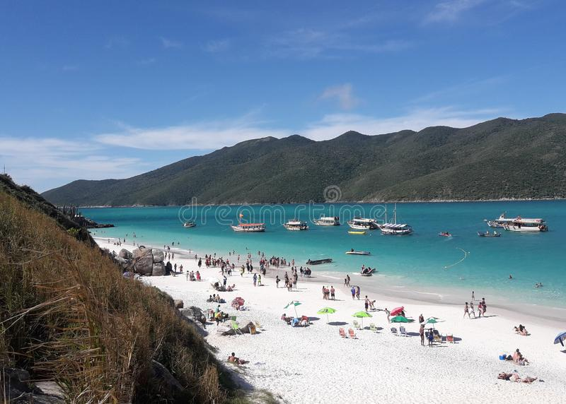 Arraial fa Cabo - bella spiaggia brasiliana sulla costa di Rio de Janeiro con la gente, le barche ed il cielo blu fotografia stock