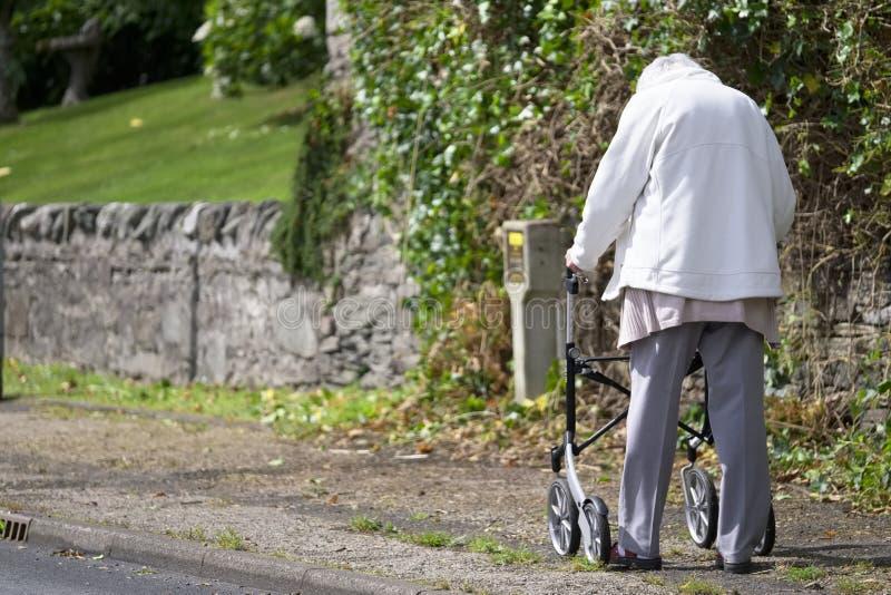 Arran, Ayrshire norte/Escócia - 10 de julho de 2019: Pessoa vulnerável idosa superior com quadro de passeio do zimmer para a mobi imagens de stock