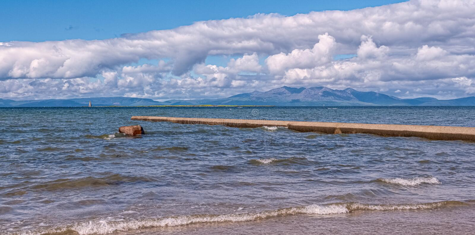 Arran on the West Coast of Scotland From the Town of Ardrossan. The Isle of Arran on a bright cloudy day looking over the River Clyde with Horse Island also in royalty free stock photos