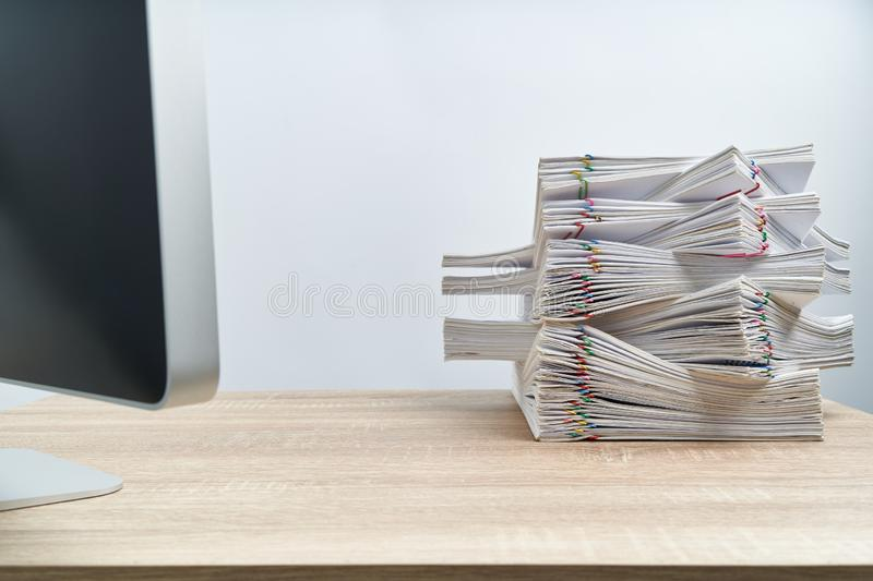 Arrange of overload paperwork report and computer on wooden table stock photos