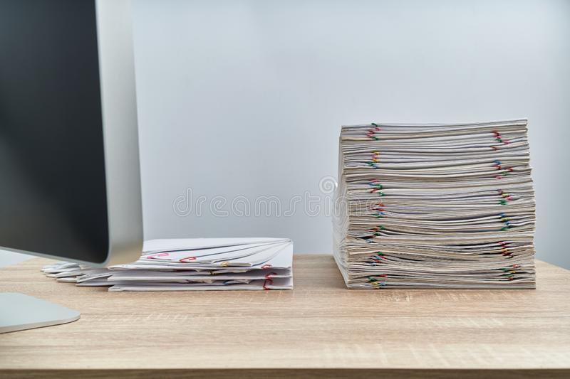 Arrange pile overload paperwork report and computer on wooden table royalty free stock photo