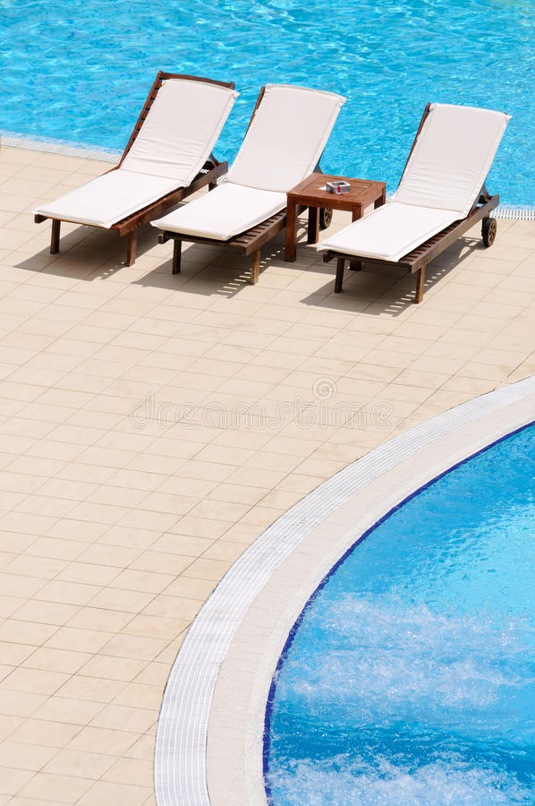Arranged chairs next to swimming pool stock image