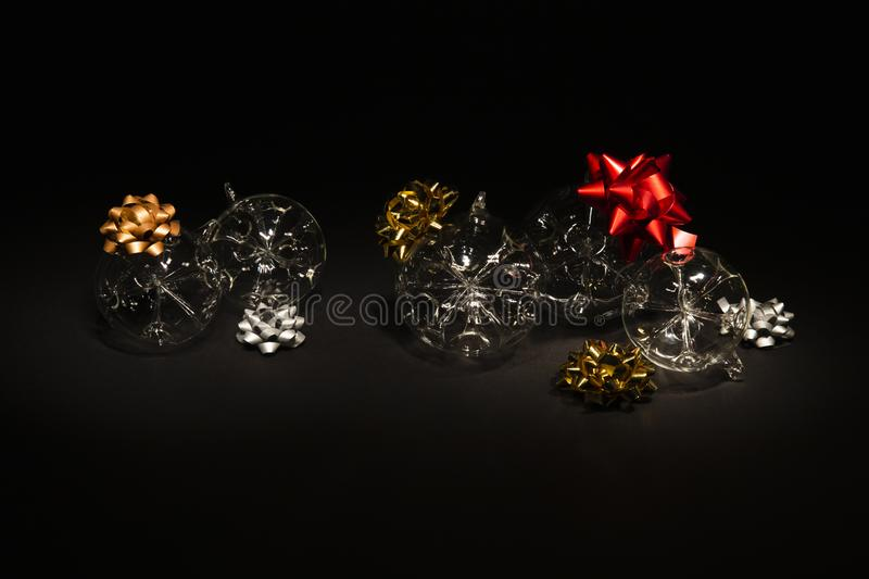 Transparent glass Christmas balls with colorful ribbons on black background stock images