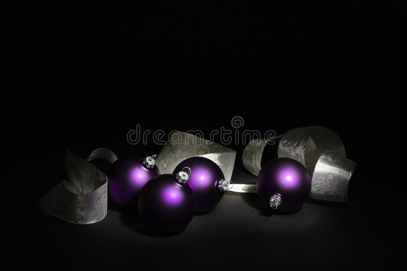 Purple Christmas balls and white ribbon on black background royalty free stock photography