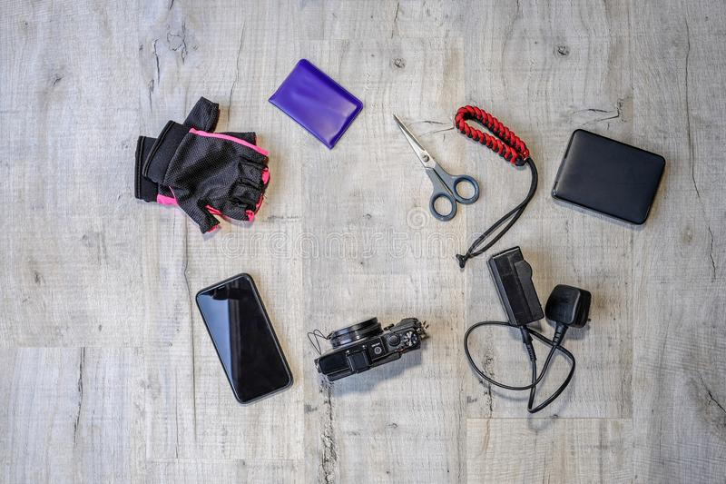 Arrangement of camera, smart phone and hardrive on a desk. Mobile phone, small camera, charger and hardrive with other essentials for a day out with your camera stock photo