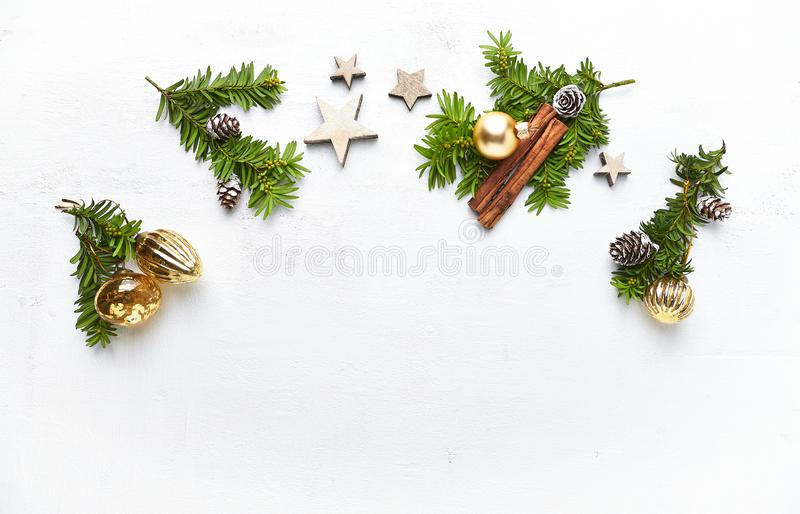 An arrangement of Chritsmas decorations, cinnamon sticks and evergreen twigs on white background. stock photography