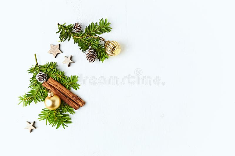 An arrangement of Chritsmas decorations, cinnamon sticks and evergreen twigs on white background. stock photos