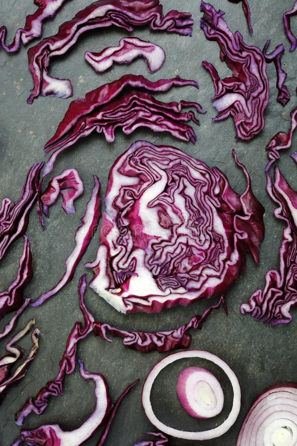 Red cabbage and red onion on slate table royalty free stock image