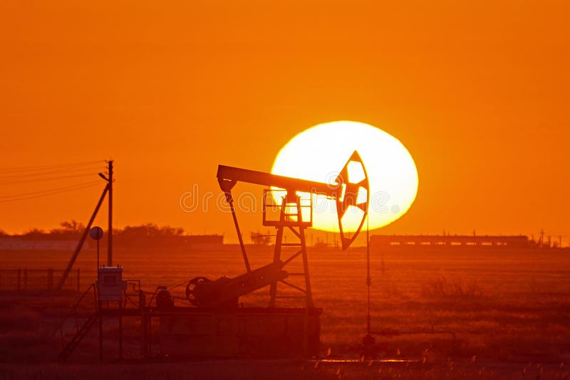Pumpjack on sunset background. A pumpjack is the overground drive for a reciprocating piston pump in an oil well. royalty free stock images