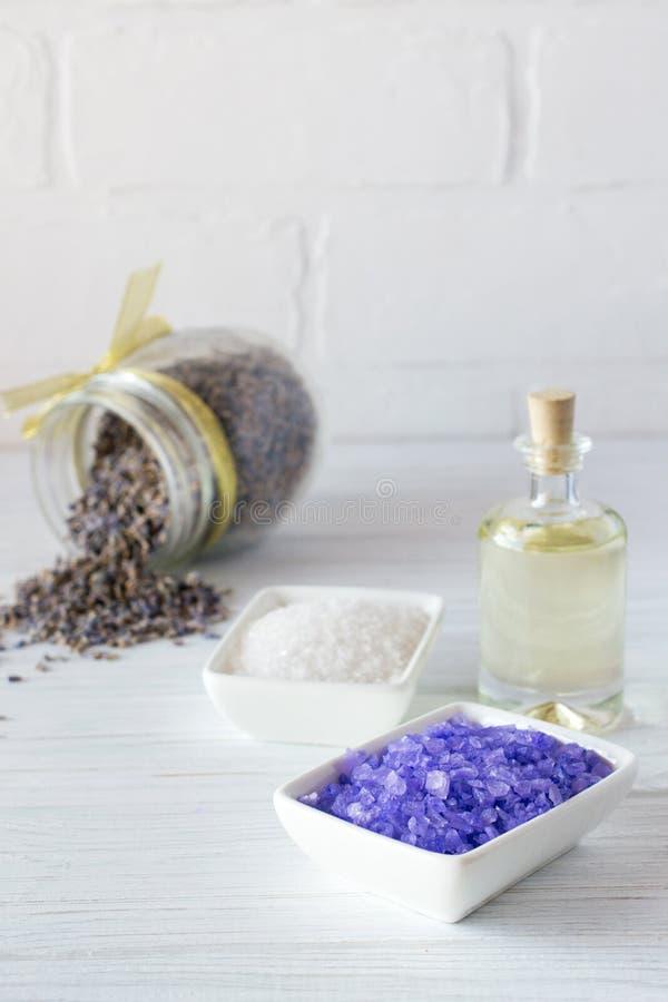 Arrangement de bien-être Le sel lilas de mer, huile de massage, lavande fleurit sur le fond en bois blanc photographie stock libre de droits