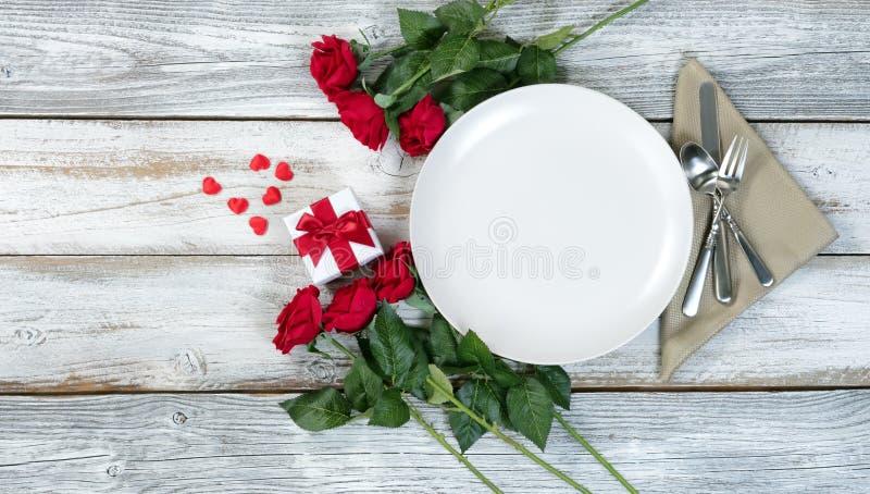 Arrangement de dîner de Valentine avec les fleurs et le cadeau sur la table blanche photo libre de droits