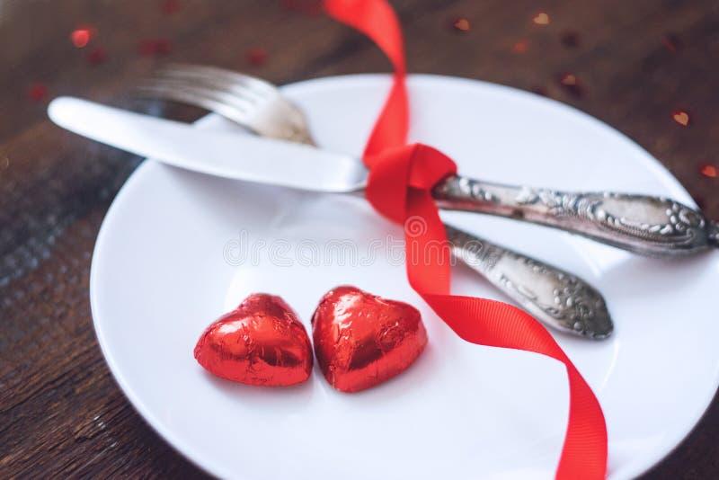 Arrangement de fête de table de Saint-Valentin, maquette avec deux bonbons au chocolat rouges à forme de coeur du plat blanc, fou photos libres de droits