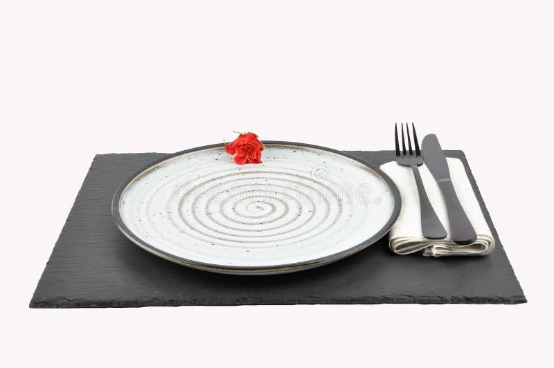 Arrangement de rose et de table de rouge sur l'ardoise d'isolement image stock