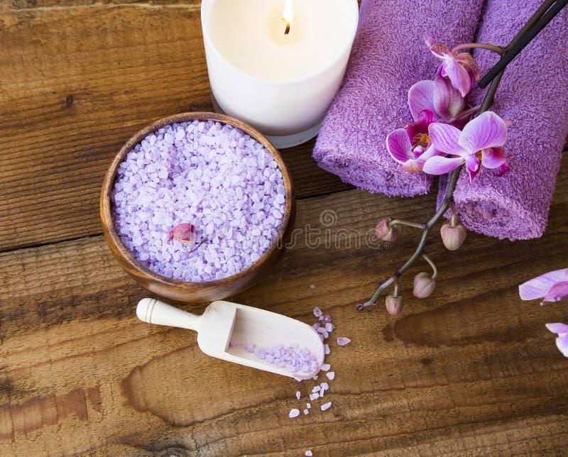 Arrangement de station thermale avec du sel de bain, orchidée, bougie, serviettes et sur le woode images libres de droits