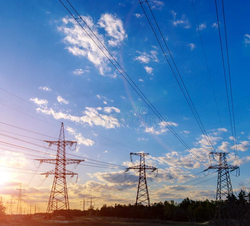 Arrangement de Sun derrière la silhouette des pylônes de l'électricité images stock