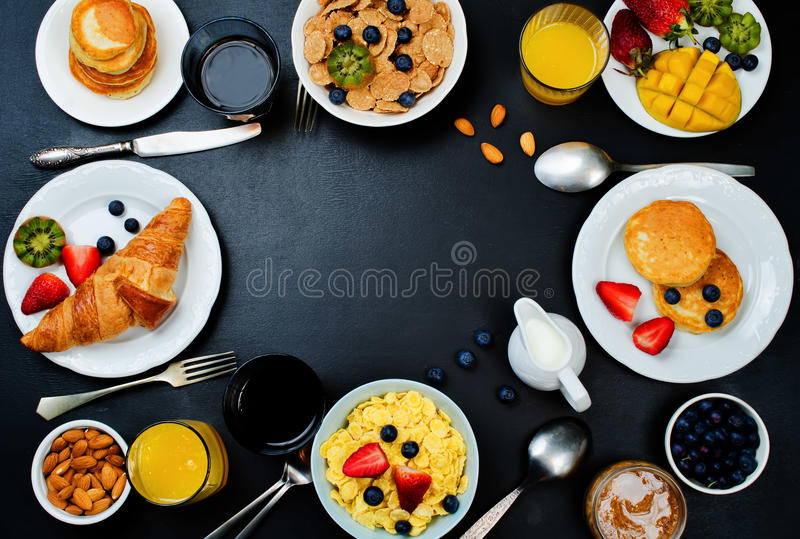 Arrangement de table de petit déjeuner avec des flocons, jus, croissants, crêpes photos libres de droits