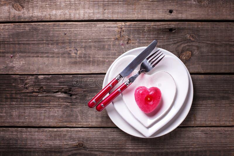 Arrangement de table de St Valentine Day Les plats blancs sous la forme de coeur, les couverts, bougie sur le cru ont donné au fo images libres de droits