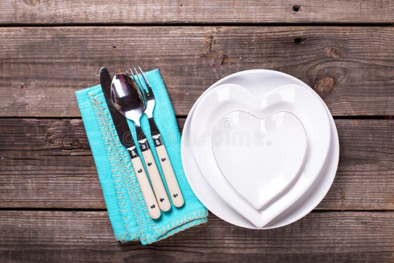 Arrangement de table de St Valentine Day Les plats blancs sous la forme de coeur, les couverts, serviette sur le cru ont donné au photographie stock libre de droits