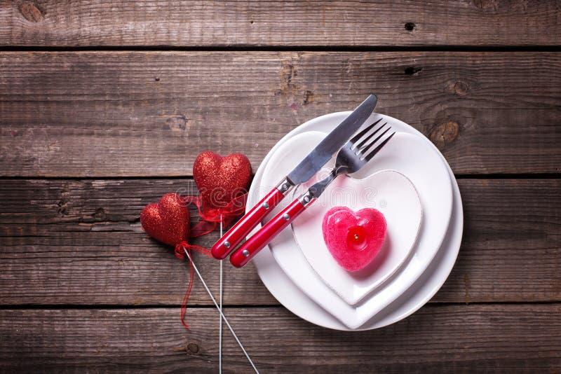Arrangement de table de St Valentine Day Plats blancs sous la forme de coeur, couverts, bougie, deux coeurs décoratifs rouges sur image libre de droits