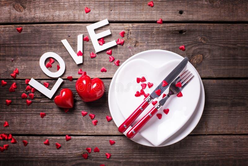 Arrangement de table de St Valentine Day Plats blancs sous la forme de coeur, de couverts, de coeurs décoratifs et d'amour de mot photos stock