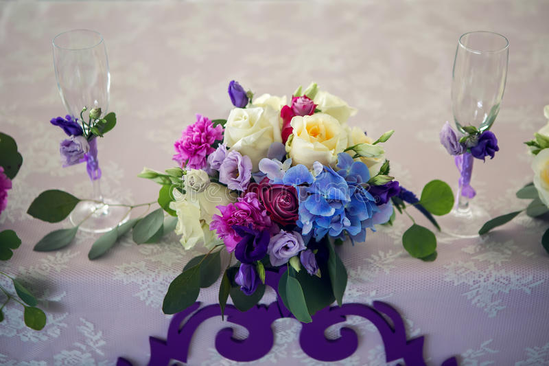 Arrangement of different flowers is on the table. With glasses of the newlyweds, wedding stock images