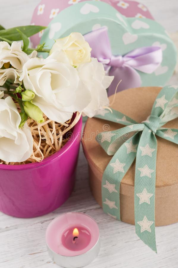 Arrangement of eustoma flowers in pot, pastel gift box. Arrangement of white eustoma flowers in purple pot, pastel gift box and pink lit candle. Greeting card stock images
