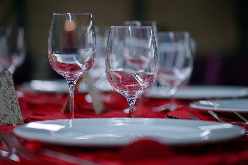 Arrangement fin de table de salle à manger avec les verres cristal blancs de porcelaine et de vin et d'eau, avec l'argenterie dan photo libre de droits