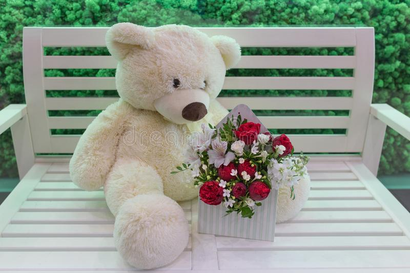 Arrangement of flowers  in a gift box in the form of an envelope on the background of a white bench and a toy teddy bear. Arrangement of flowers Flowers: rose stock images