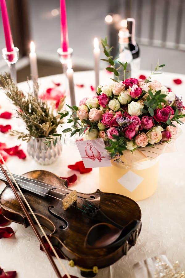 Arrangement romantique de table avec de belles fleurs dans la boîte, les pétales de rose et le violon photo stock