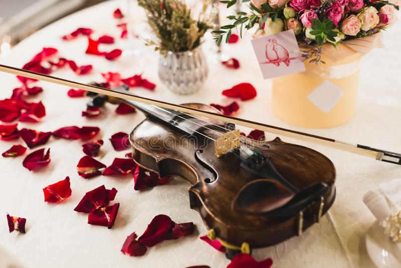 Arrangement romantique de table avec de belles fleurs dans la boîte, les pétales de rose et le violon image stock