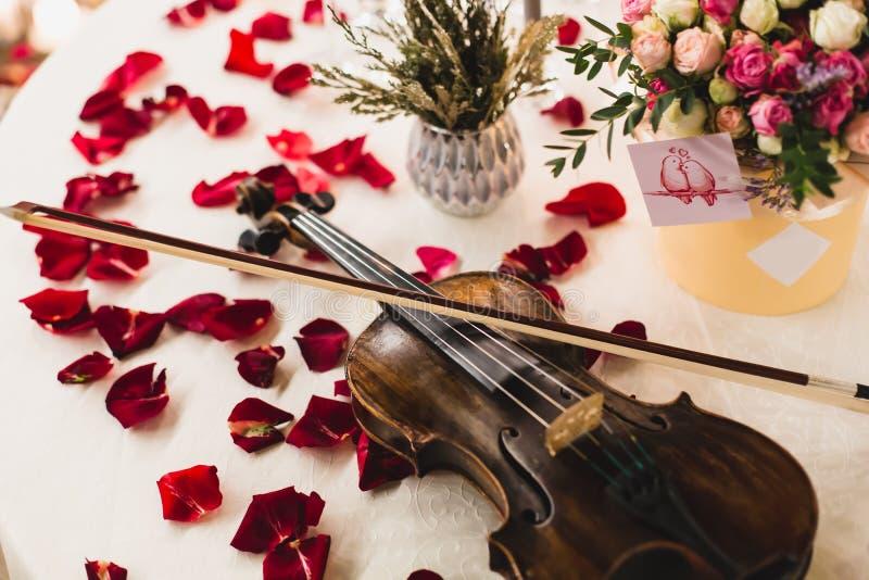 Arrangement romantique de table avec de belles fleurs dans la boîte, les pétales de rose et le violon photo libre de droits