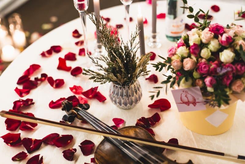 Arrangement romantique de table avec de belles fleurs dans la boîte, les pétales de rose et le violon photos stock