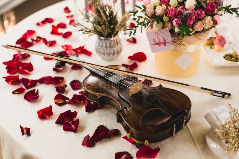 Arrangement romantique de table avec de belles fleurs dans la boîte, les pétales de rose et le violon photographie stock libre de droits
