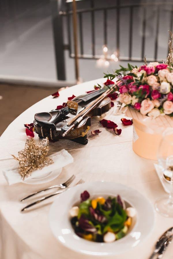 Arrangement romantique de table avec de belles fleurs dans la boîte, les pétales de rose et le violon photographie stock
