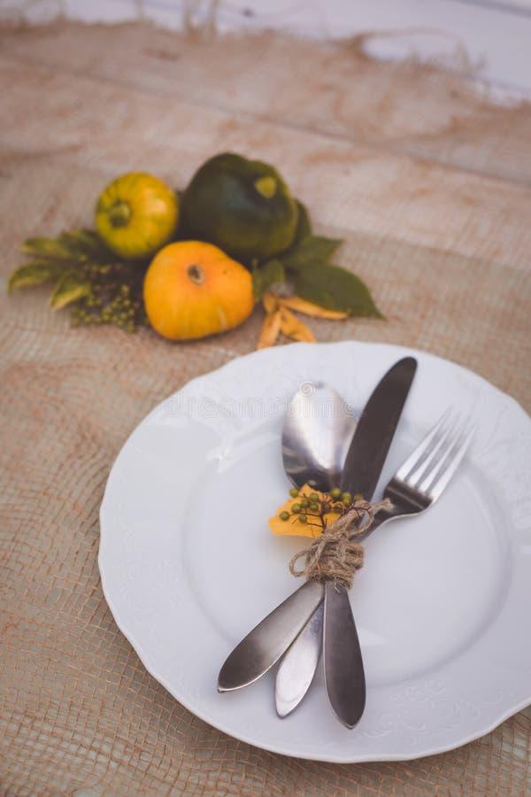 Arrangement saisonnier de table avec de petits potirons et feuilles de jaune et de vert photos stock